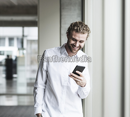 smiling young businessman looking at cell