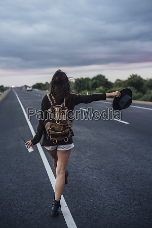 back view of hitchhiking young woman