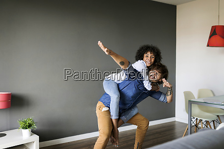 posing man carrying girlfriend piggyback at