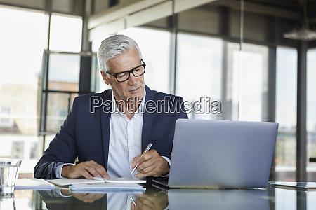 businessman working at laptop taking notes