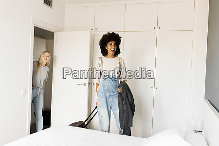 two happy women with baggage arriving