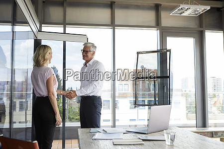 businessman and woman shaking hands in