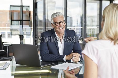 businessman snd woman sitting in office