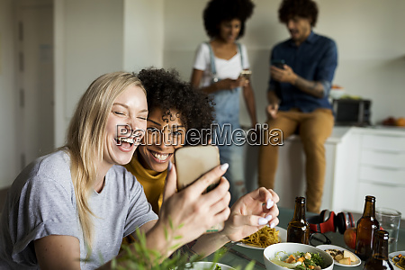 happy girlfriends with cell phone sitting