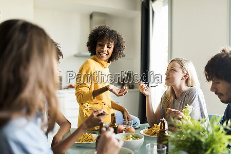 friends sitting at table talking eating