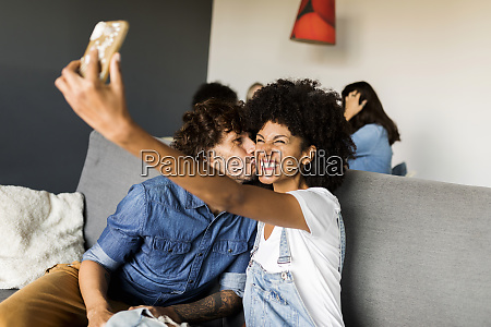 happy couple sitting on couch taking