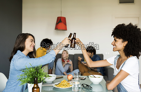 smiling friends clinking beer bottles at