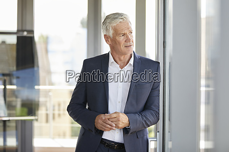 worried businessman standing by window thinking