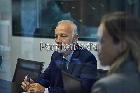 portrait of senior businessman listening in