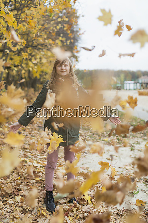 playful tween girl playing in autumn