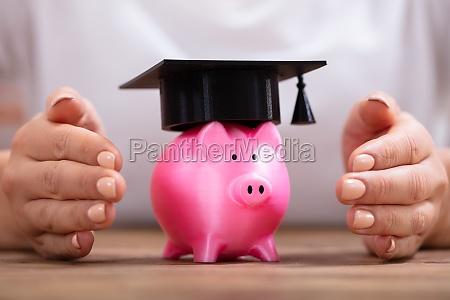 frau beschuetzt piggybank mit graduiertenkappe