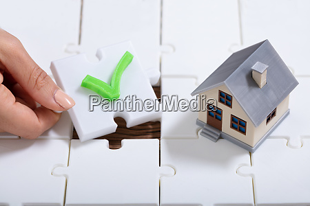 person holding tick puzzle pieces near