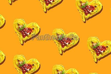 dekorative herzen aus spaghetti auf orange