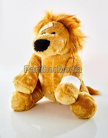 ill plush toy lion with bandaged