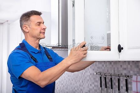 handyman fitting cabinet door