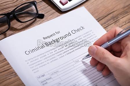 person filling criminal background check form
