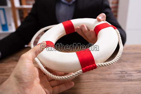 businesspeople holding a lifebuoy in hands