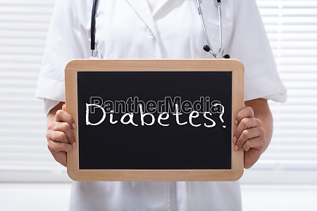 doctor holding holzschiefer mit text diabetes