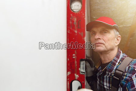 man holding level against interior drywall