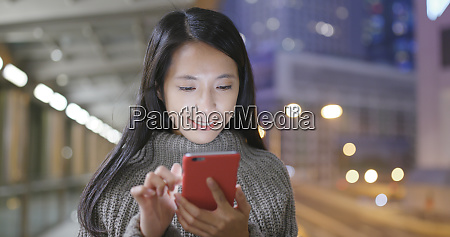 woman using cellphone in city at