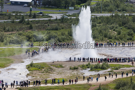 tourists watch the eruption of the