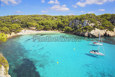 view of cala macarella and sailboats