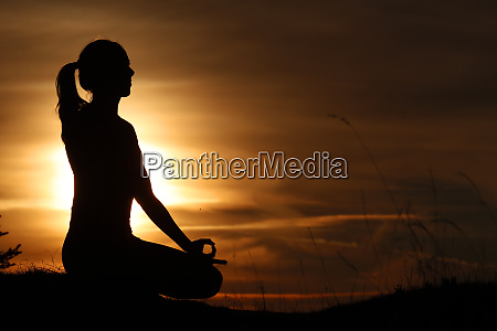 silhouette einer frau in lotusposition yoga