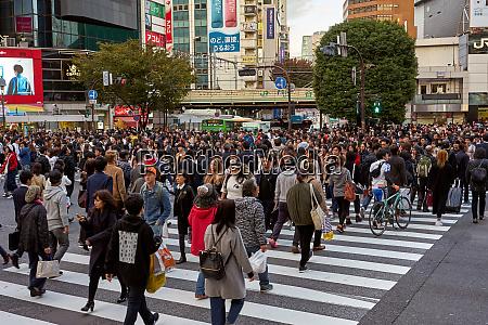 menschenmassen die durch die shibuya crossing