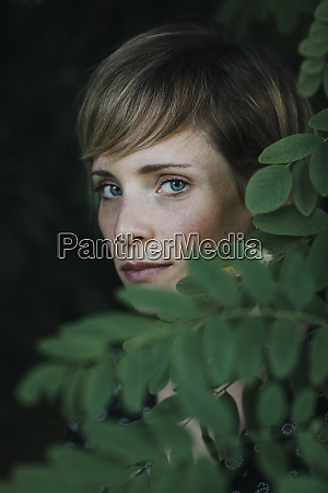 portrait of a woman behind leaves