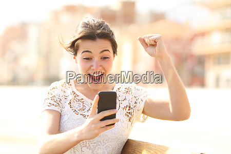 excited woman reading amazing news on