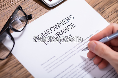 person filling homeowners insurance policy form