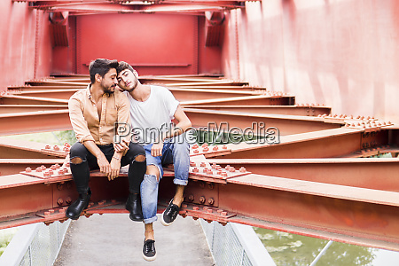 young gay couple in love sitting