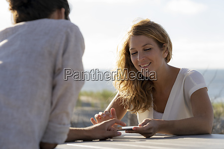 young couple using digital tablet sitting