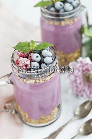 zwei glaeser joghurt mit erdnussgranola aronia