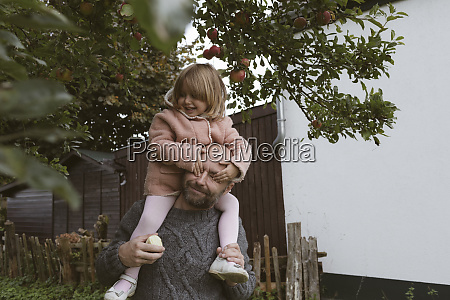 father carrying his little daughter on