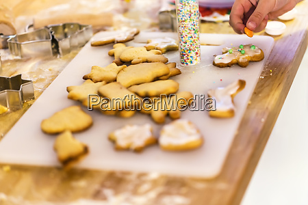 girls hand decorating christmas cookies