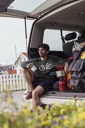 junger mann sitzt im wohnmobil und