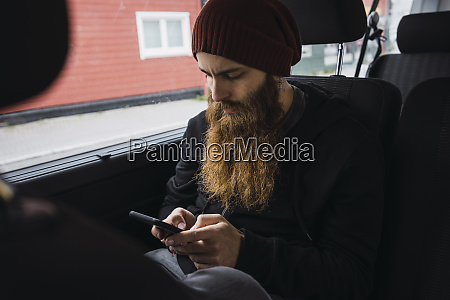 bearded young man sitting on back