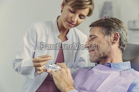 dentist explaining dental bridge on a