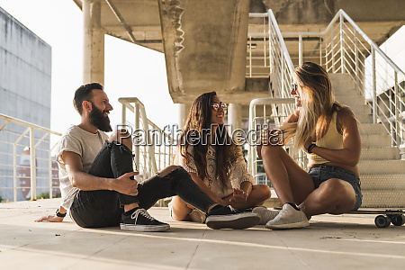 friends with skateboard sitting down relaxing