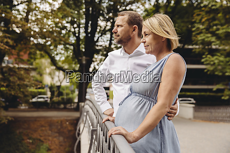 mature pregnant couple standing at bridge
