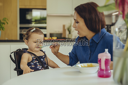 mother helping disgusted baby daughter eating