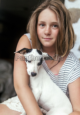portrait of freckled girl with puppy