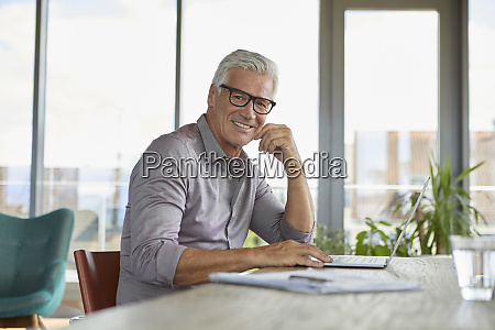portrait of smiling mature man using