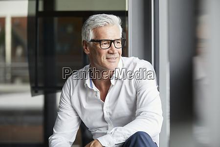 serene businessman sitting on ground looking