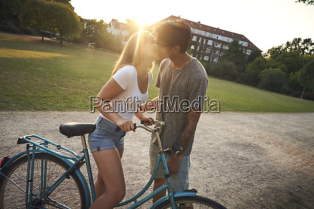 young woman with bicycle kissing her