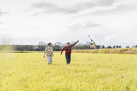 happy senior couple flying kite in