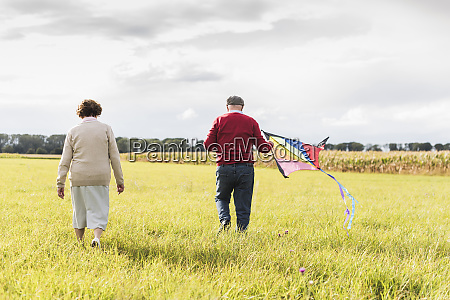 senior couple walking with kite in