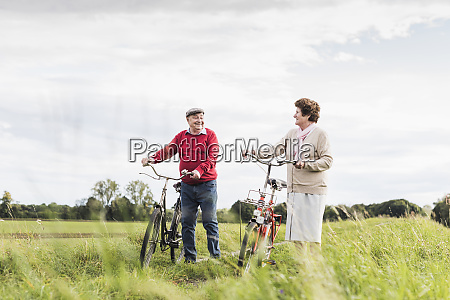 senior couple pushing bicycles in rural
