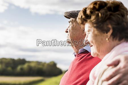 senior couple embracing in rural landscape